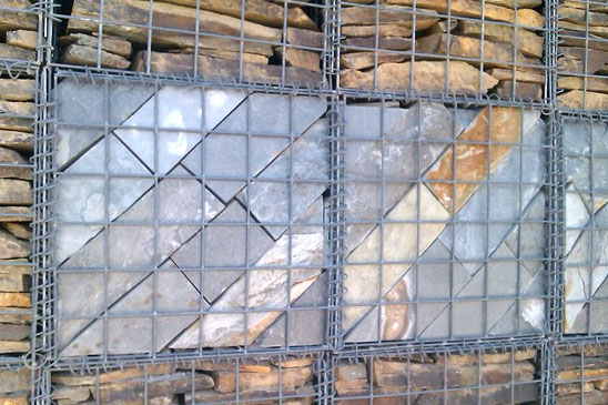 Gabion wall filled with coursed stone but a slate feature incorporated